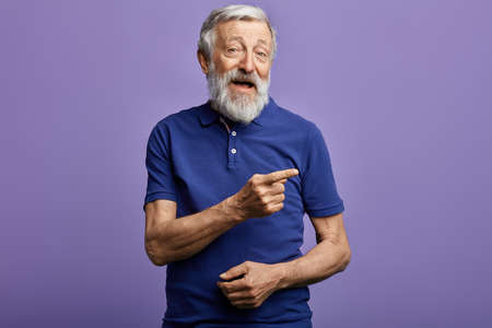 positive man pointing with hand and finger to the side. look here, happy old man showing direction, pension is being given here. this is the right way.