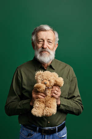 sweet handsome senior gentleman holding a teddy bear in the studio with green wall, close up portrait, old man has prepared a gift for his granddaughter on Birthday party. surprise concept