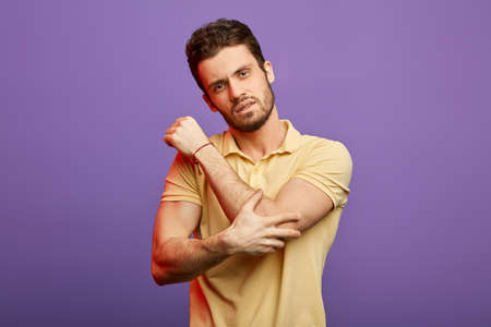 attractive brunette man holding his elbow and looking at the camera. close up photo. studio shot.man has boken his arm.accident concept Фото со стока