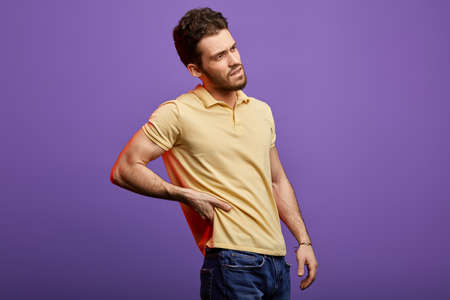 handsome bearded unhappy man holding his back. close up photo. isolated blue background. emotion and feeling .