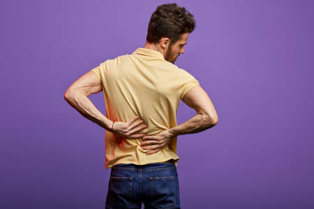 young man suffering from backache. close up back view photo. studio shot.disk herniation, slipped disk Фото со стока