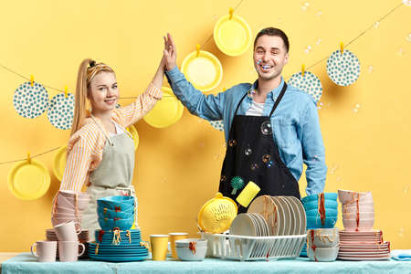happy attractive man and woman in aprons with raised arms holding each other and looking to the camera. friendly family. work connecting people. clean colorful plates hanging in the background photo