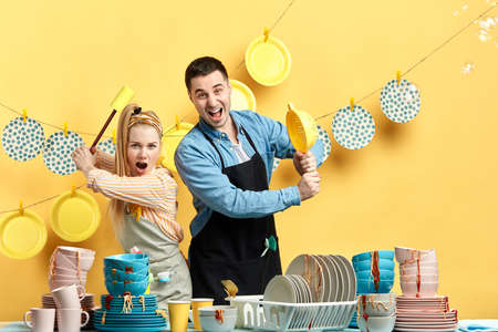 Funny positive couple in aprons having fun during doing housework and cleaning. crazy man and woman fighting with dirty cutlery.were going to wash your dishes.