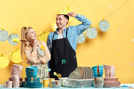 crazy positive man putting on the colander while his pensive smiling wife holding a washing tool and watching him, close up photo. studio shot.