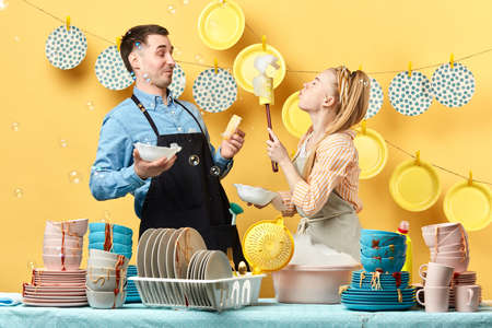 funny young blonde woman with closed eyes blowing foam to her boyfriend in the kitchen, side view photo. happy pastime concept