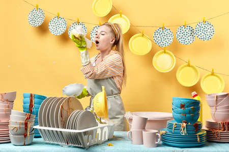 attractive nice girl with ponytail blowing the bubbles in the kitchen with yellow wall and disposable plates on it.funny time. Фото со стока