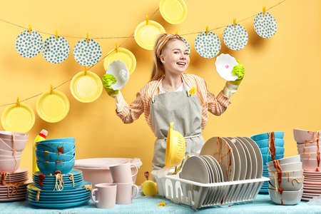 positive housekeeper comparing differen dish soaps, woman with raised arms holding clean plates . result of washing, close up photo. isolated yellow background