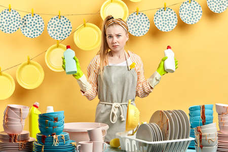 unhappy serious woman with washing up liquids posing to the camera. close up photo. studio shot.job, profession, lifestyle, cleaning time. housekeeping