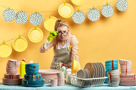 emotional blonde housewife with sceptical expression looking at the camera. close up photo. funny woman in glasses looking for effective dishwashing liquid.