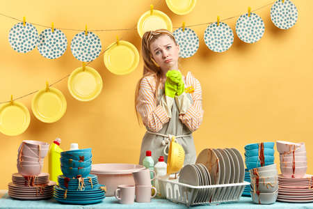 beautiful depressed woman with miserable look posing to the camera, isolated yellow background, woman is fed up with housework