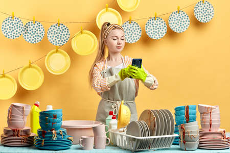 attractive blonde woman taking pictures of herself, taking selfies in the modern kitchen room. lifestyle, free time, spare time
