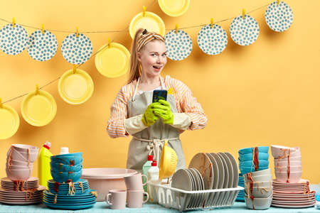 cheerful young woman having a chat with a boyfriend while cleaning the kitchen. close up portrait. Фото со стока