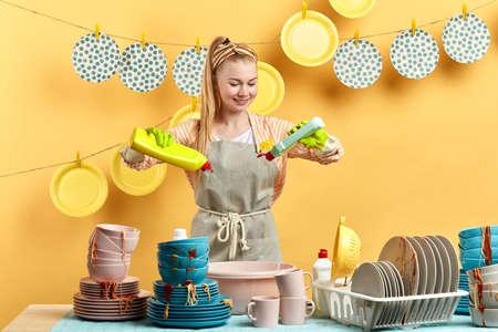 hardworking blonde woman mixing different dishwashing detergents. close up photo.daily routine, housekeeping