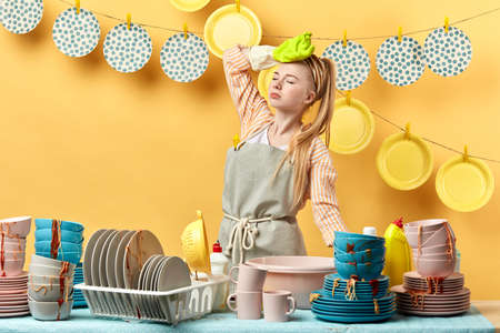 housewife holding her head, having headache, girl having a break, having a rest while washing the dishes in the kitchen with yellow wall, housewife overloaded with much work