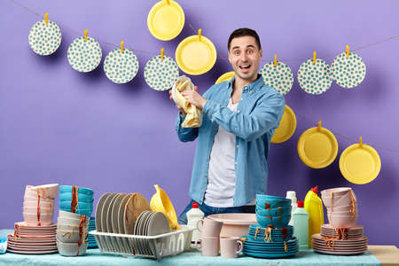 handsome cheerful man wiping plate with towel in the kitchen with blue wall. housework, free time, spare time, lifestyle. husband helping her wife at home