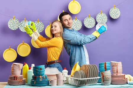 Young positive happy couple standing back to back and washing dishes. close up photo. hobby, lifestyle, hygiene concept