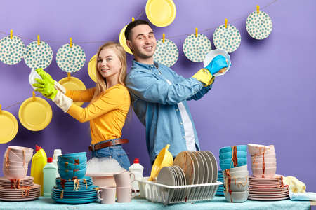 cheerful happy family enjoying working in the kitchen. happiness, feeling, emotion concept, hardworking wife and husband standing behind the table full of dirty used cutlery Фото со стока