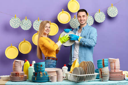 young blonde woman in yellow sweater and brunette man in T-shirt and jacket washing the dishes at home.