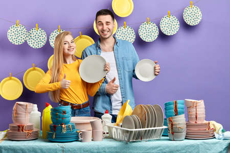 positive young awesome blonde woman and black-haired man showing thumbs up , holding clean plates Фото со стока