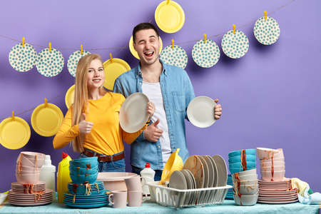 Young smiling woman and man showing thumbs up to the camera, effective good dishwashing liquid for dirty tablewear