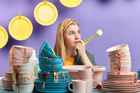 young beautifulpensive thoughtful housewife holding a brush and sitting behind the table with a pile of dirty dishes, idea, plan concept Stockfoto