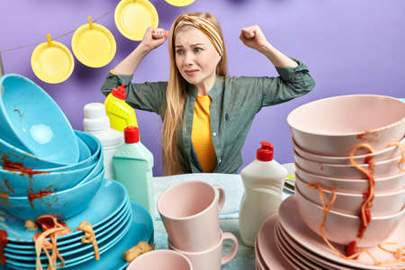 waht dirty plates.upset caucasian woman looks with dissatisfcation at messy table, feds up of washing cutlery