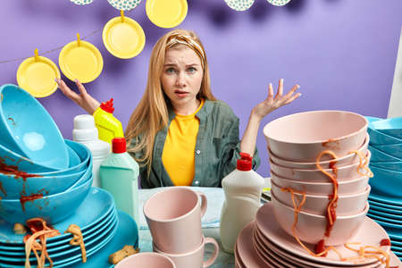 puzzled blonde girl in stylish casual clothe sitting behind the messy kitchen table and looking at the camera. close up photo, domestic chores