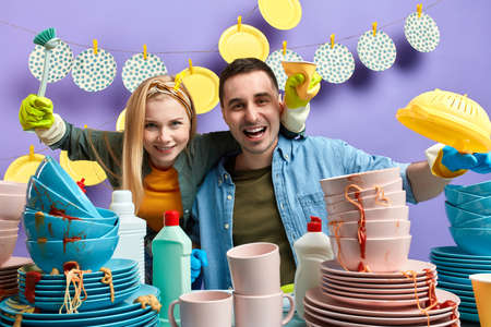 cleaning washing service concept, cheerful happy woman and man standing behind the messy table and looking at the camera. close up photo