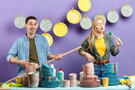 young mad couple having fun in the kitchen with modern interior. studio shot. talent concept Фото со стока
