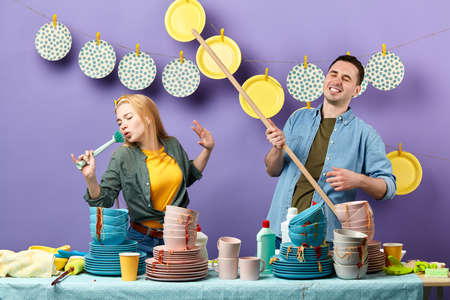 awesome couple singing while doing household chores.housework and housekeeping concept.