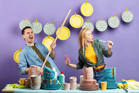 young emotional couple using brush and broom to dance and sing while doing washing indoors.