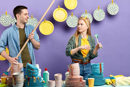 serious woman looking at smiling man while working in the kitchen, guy trying to flirt with unhappy girl