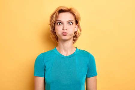 Mujer joven irritada molesta en camiseta azul que sopla sus mejillas, frunciendo el ceño, sintiéndose frustrada con algo. fondo amarillo aislado