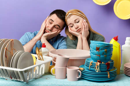 unhappy tired sleepy couple leaning on the table full of dirty plates and cups. close up photo. laziness concept