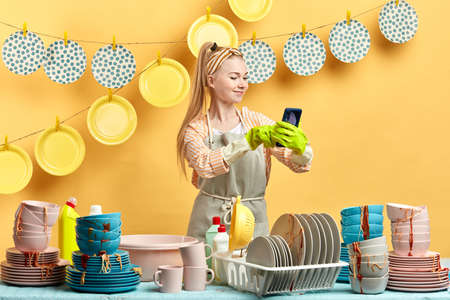 cheerful smiling hardworking woman taking picture of her clean plaets which are hanging on the clothespins. selfie with washed plates.interest and hobby concept