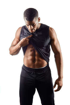 young muscular athlete lifting his T-shirt and looking at his stomach. closeup portrait. isolated white background. motivation