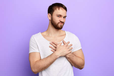 emotional handsome young man puts hands on chest sincerely requesting God posing isolated on blue studio background, man expressing thanks. close up portrait.