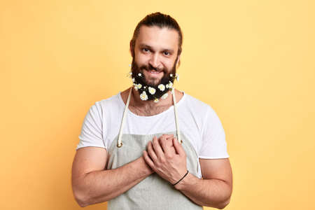 emotional sweet man with a beard decorated with flowers showing his affection. garderner fell in lovee. close up portrait. isolated yellow background I love you