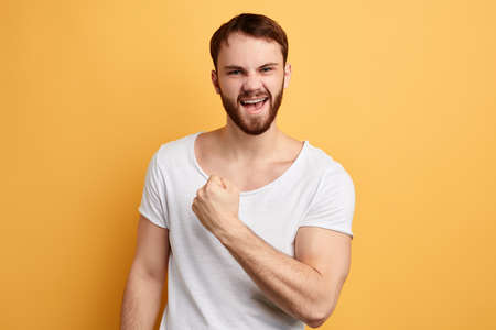 Cheerful excited happy man wearing white t-shirt celebrating successstanding isolated over yellow background,close up photo. emotion and feeling.Ive done it