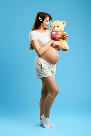 pleasant attrctive woman with a big belly olaying with teddy bear. full length photo. isolated blue background. studio shot. entertainment concept Banco de Imagens