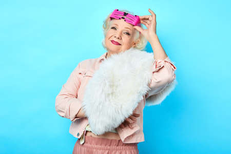 trendy pretty senior lady in fashionable clothes with funny glasses on her forehead posing to the camera. isolated blue background.