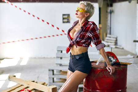 awesome stylish female builder in trendy glasses looking up, dreaming, enjoying life. lifestyle, free time, spare time . close up side view photo
