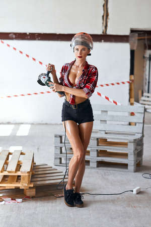 gorgeous woman in stylish shorts and shirt using machine for grinding. full length photo. shopping , sale, business