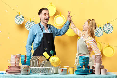 Beautiful active young hardworking couple is giving high five and smiling in the kitchen, isolated yellow background, good job. well done
