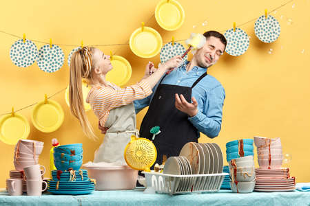 childish pleasant cheerful girl smearing her boyrirnds face with foam, they are standing behind table with dirty plates, bowls and cups, close up photo
