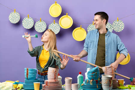 beautiful blonde woman pretends to sing song with brush and smiling young man plays with mop like guitar in the kitchen with blue wall.