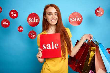 charming ginger girl with many packages inviting to do the shopping with fantastic, unreal sales. close up portrait. isolated blue background. studio shot.