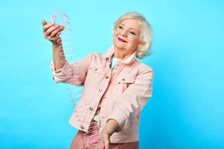 old funny beautiful cool woman playing with a slinky,isolated on blue. close up portrait. studio shot. entertainment, free time, spare time, lifestyle