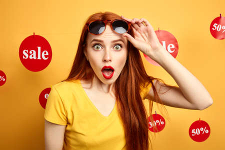 girl with sunglasses on her forehead cannot believe in huge sales. close up photo. isolated yellow background, studio shot.surprise. shock concept, woman claims a discount