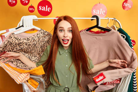 Beautiful young woman expressing positive emotion in front of rack with hangers. close up photo